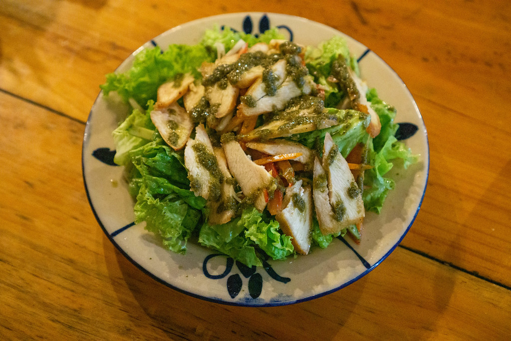 Top View Food Photo of Grilled Chicken Salad with Carrots and Dressing on a Plate in a Restaurant