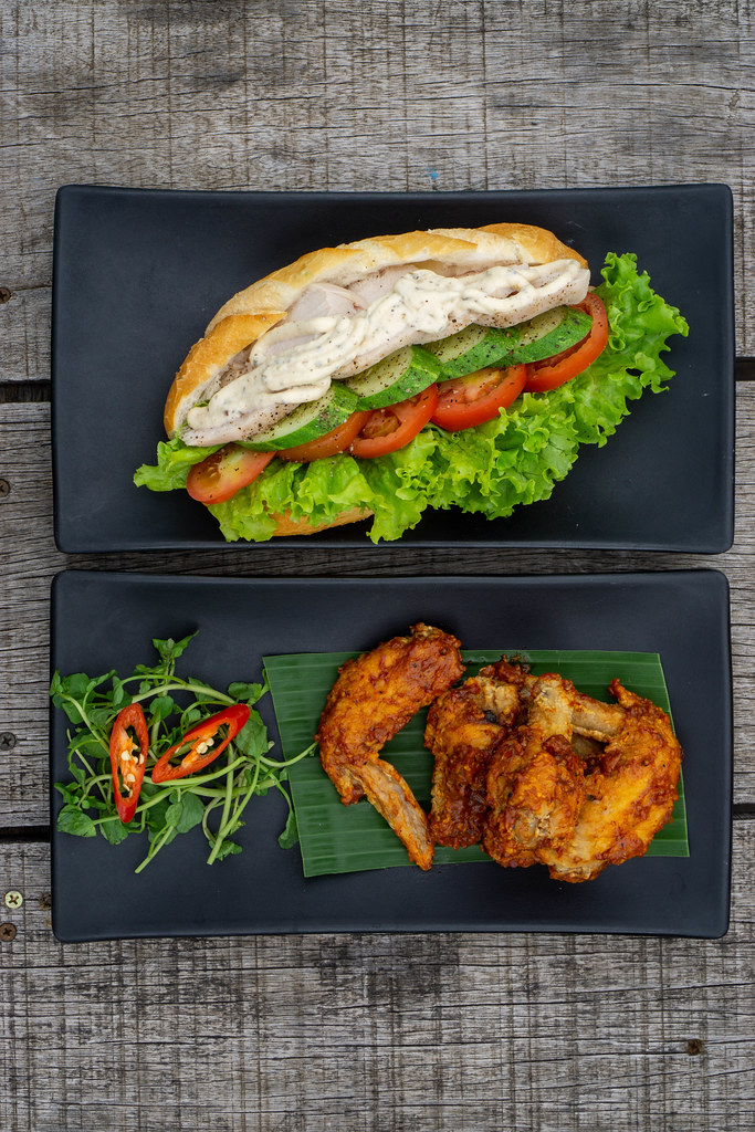 Top View Food Photo of Grilled Chicken Sandwich with Cucumber, Tomato and Lettuce and Spicy Buffalo Chicken Wings on a Wooden Table