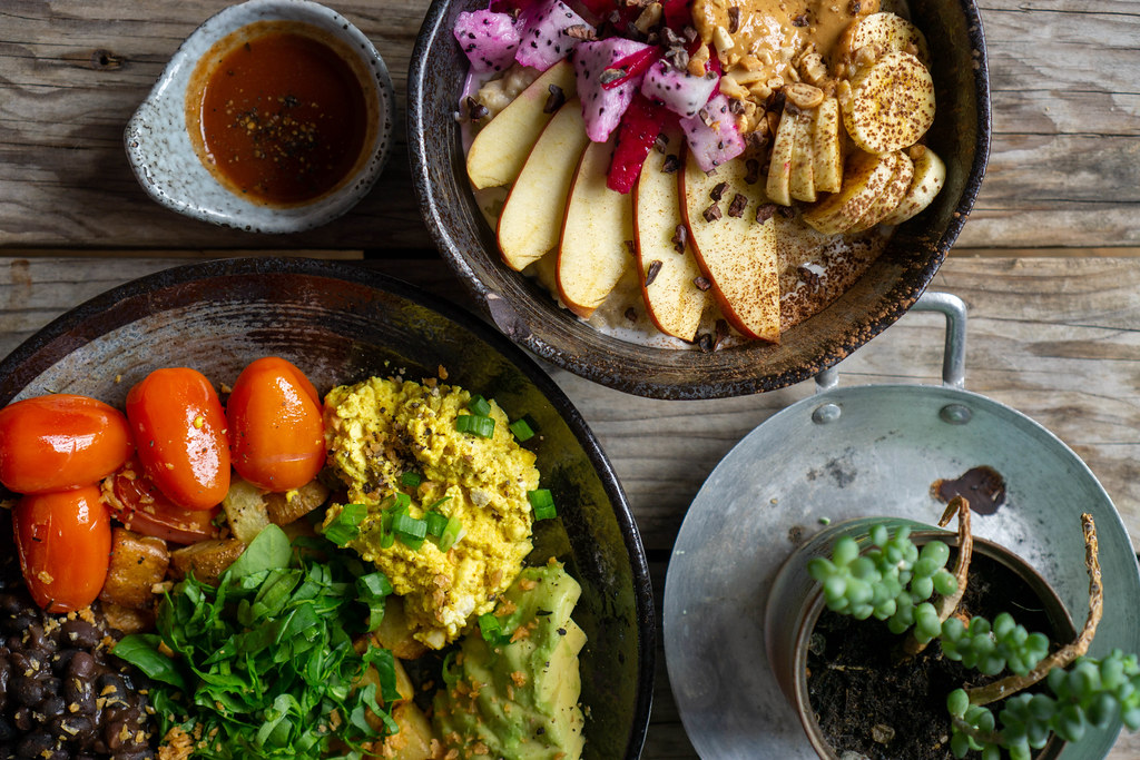 Top View Food Photo of Healthy Vegan Meal with Scrambled Tofu, Cherry, Tomatoes, Avocado, Black Beans and Porridge with Fresh Fruits