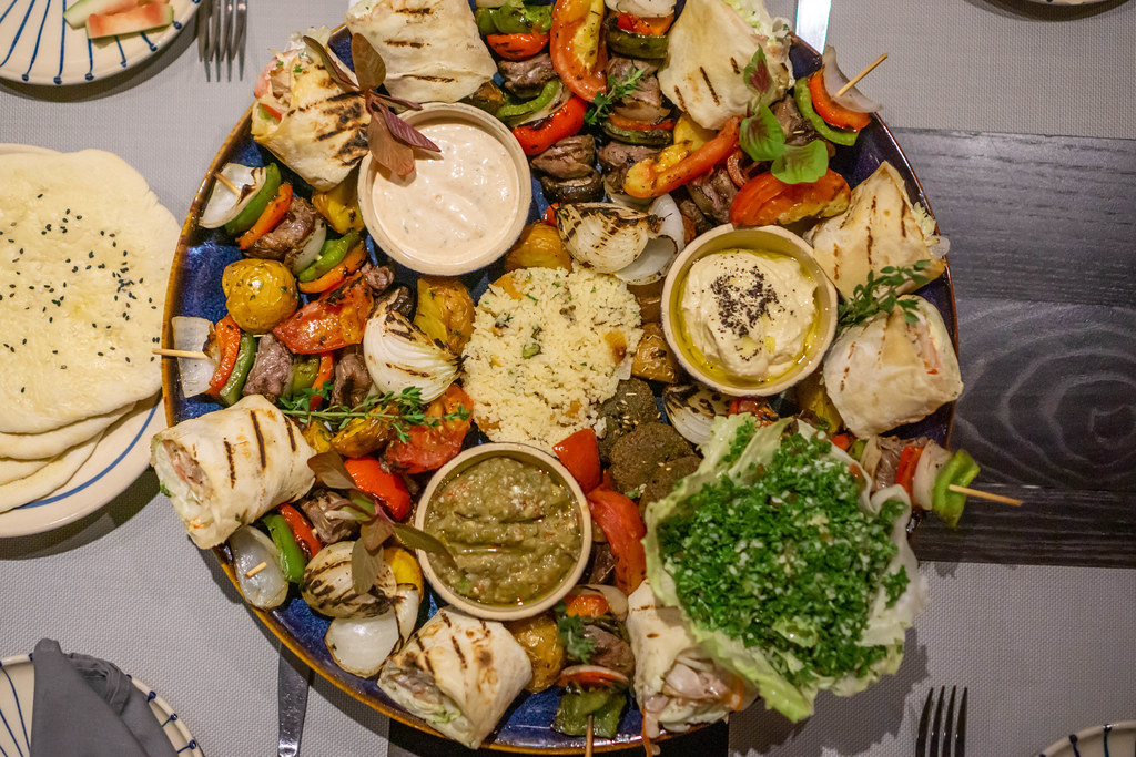 Top View Food Photo of Middle Eastern Sultan Platter with many different kinds of Foods such as Couscous, Hummus, Falafel, Beef Kebab, Chicken Shawama, Grilled Vegetables, Pita Bread and Sauces