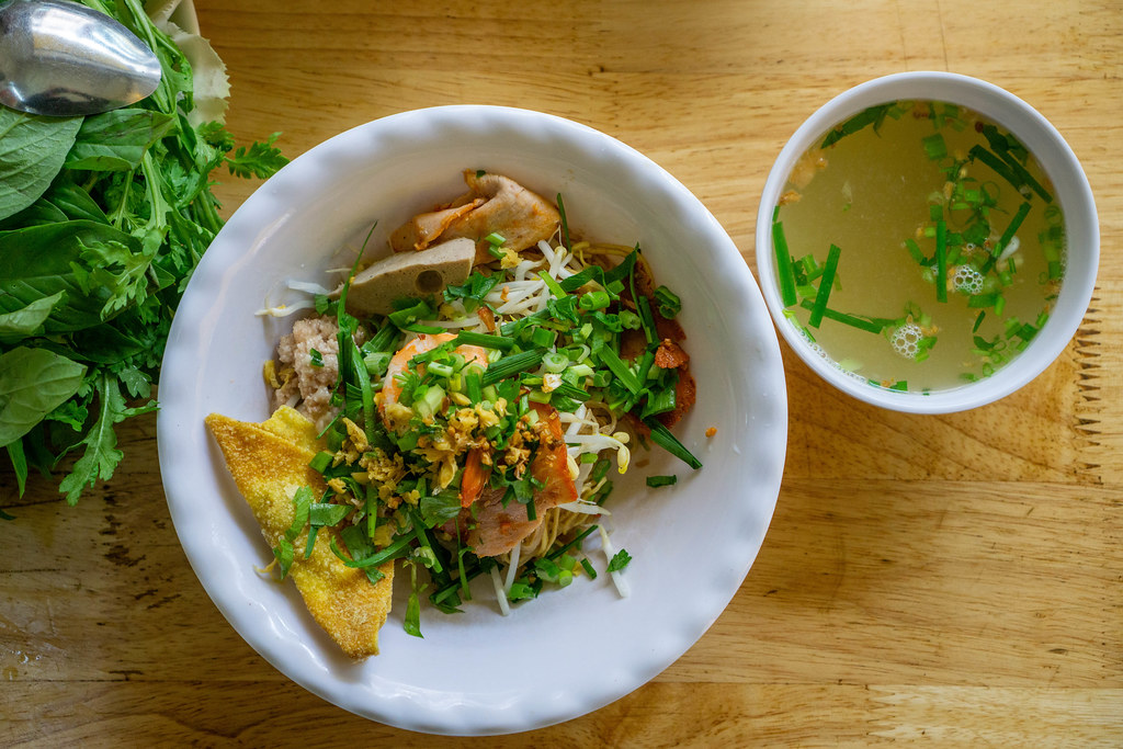 Top View Food Photo of Vietnamese Dry Hu Tieu Noodles with Pork, Shrimp, Herbs, Fried Onion and Soup on a Wooden Table in a Restaurant