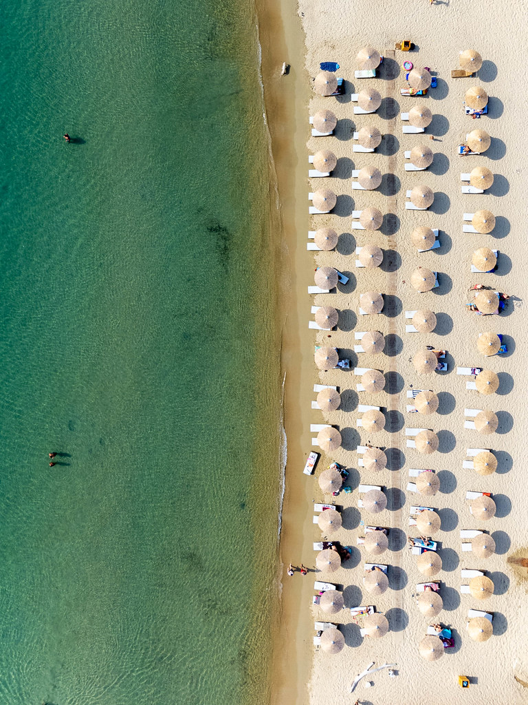 Top view: four rows of parasols on fine white sand beach with turquoise waters on Tsoungria, Greece