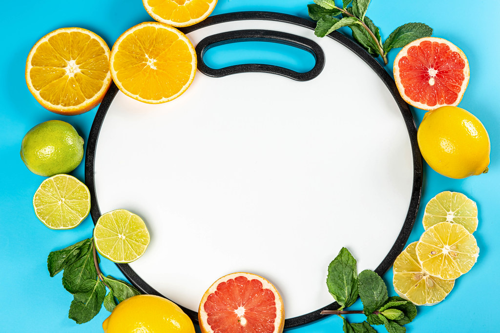 Top view, frame with fresh citrus fruits with mint on blue background with white kitchen board in the middle