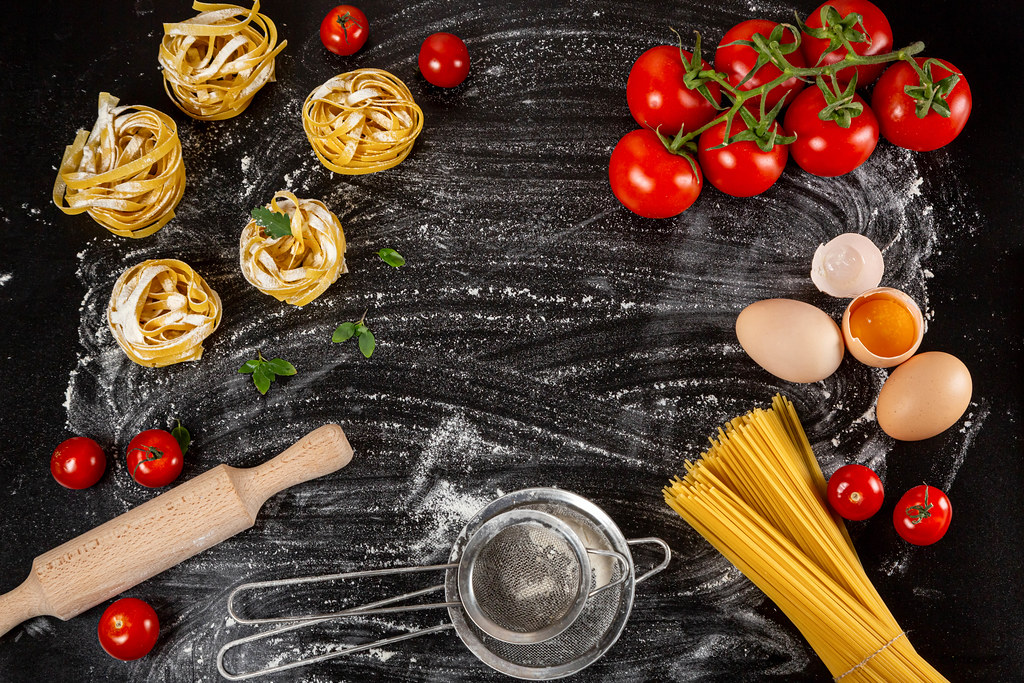 Top view, frame with Italian food products on dark background with flour