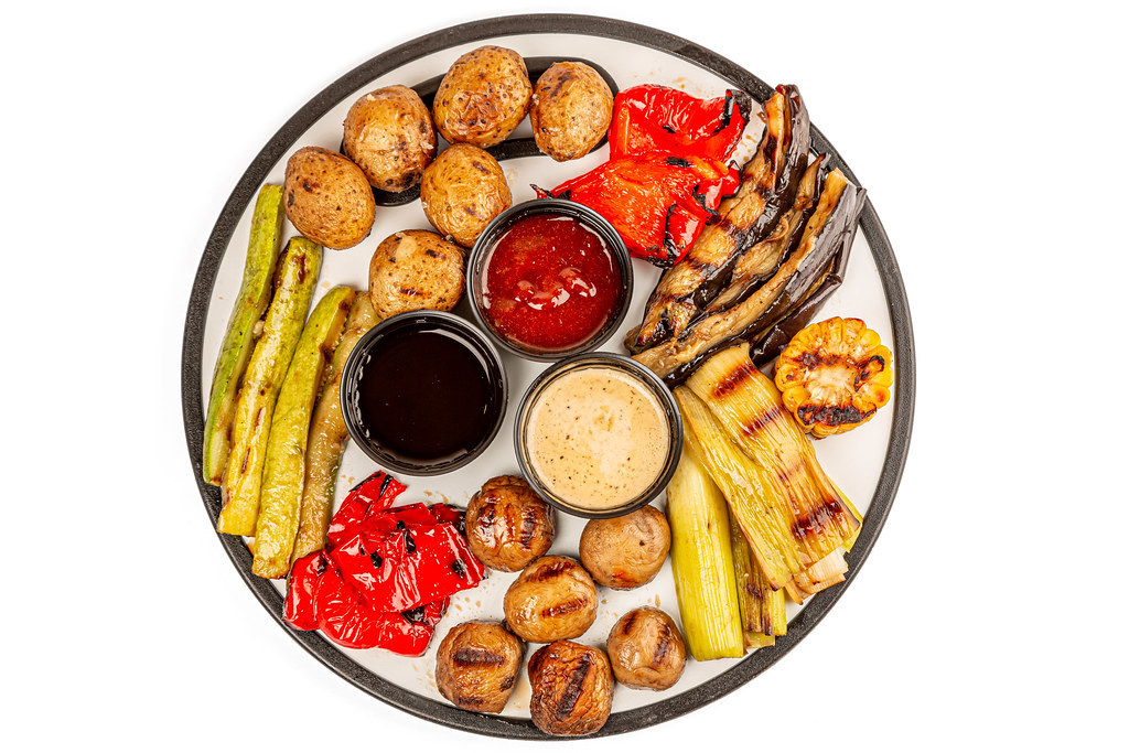 Top view, fresh grilled vegetables and mushrooms with three sauces on a round kitchen board