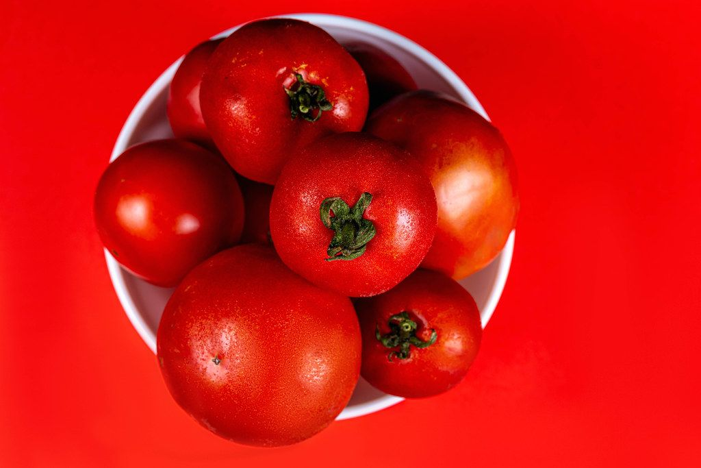 Top view, fresh red tomatoes in a bowl on a red background