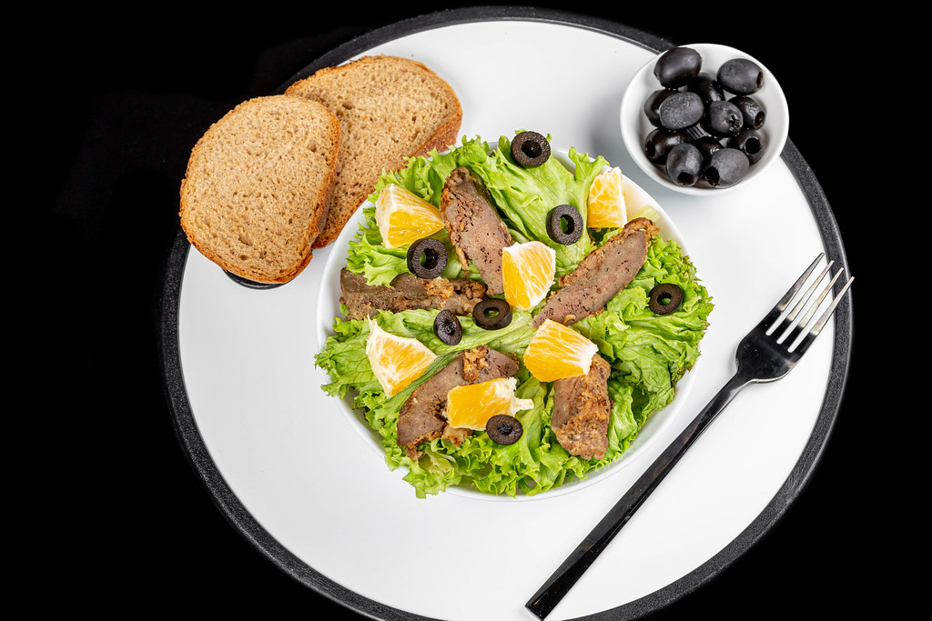 Top view, fresh salad with lettuce, orange and beef liver