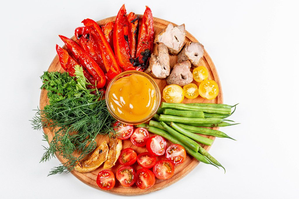 Top view, fresh vegetables, parsley, dill with grilled vegetables and meat on a round wooden kitchen board
