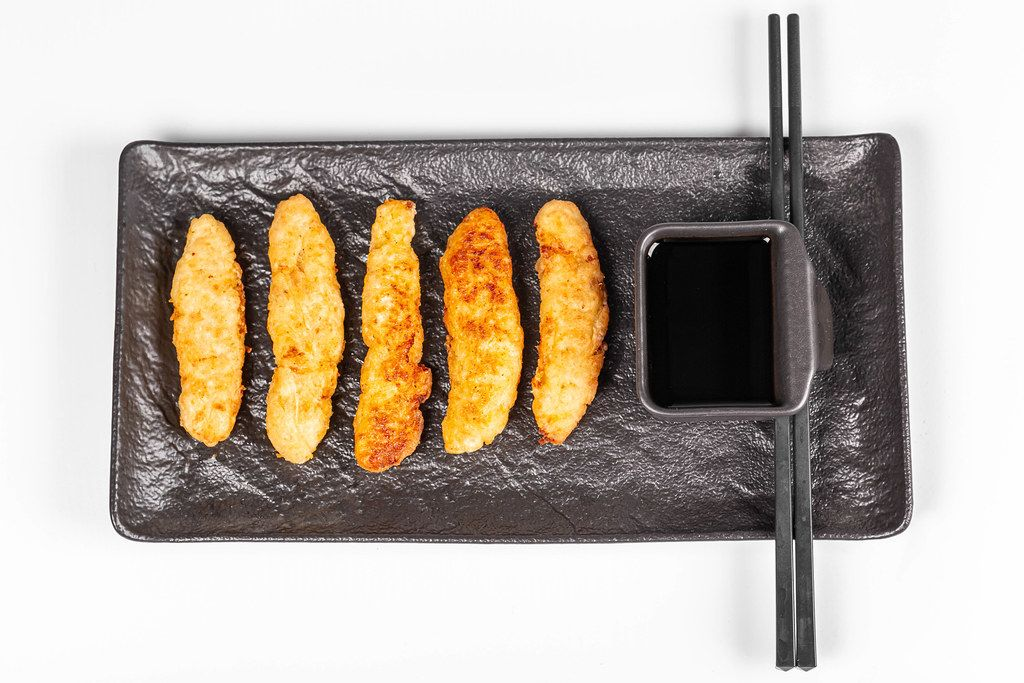 Top view, fried fish sticks with soy sauce and chopsticks
