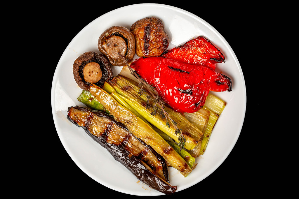 Top view, grilled vegetables and mushrooms on white plate, black background