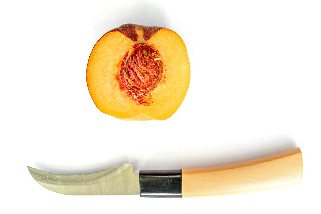 Top view, half of ripe peach with a knife