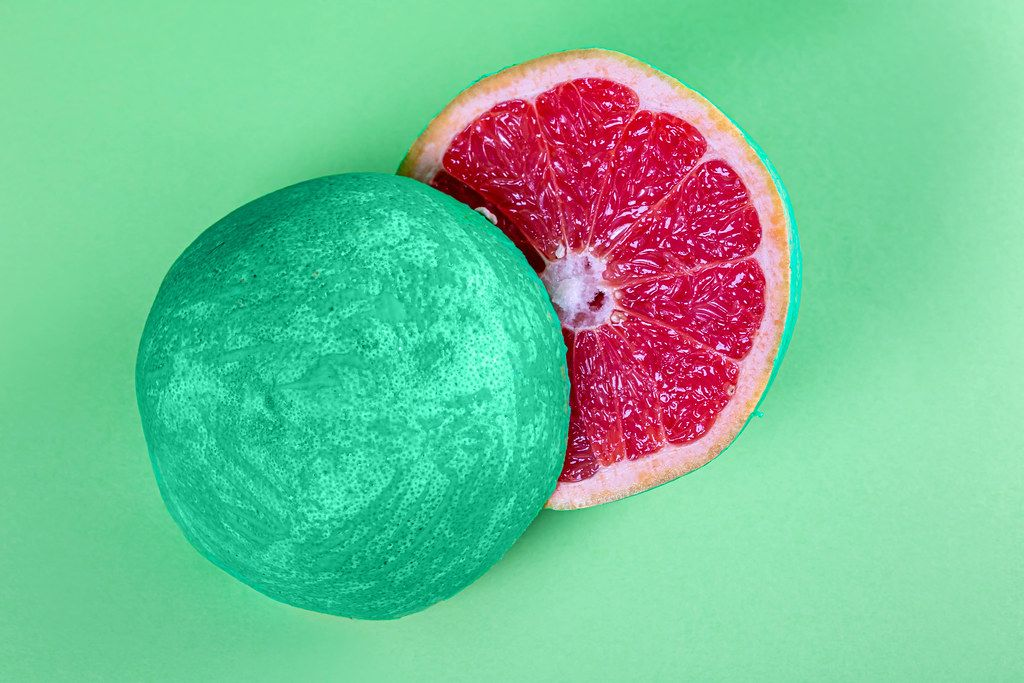 Top view, halved grapefruit with green peel on green background