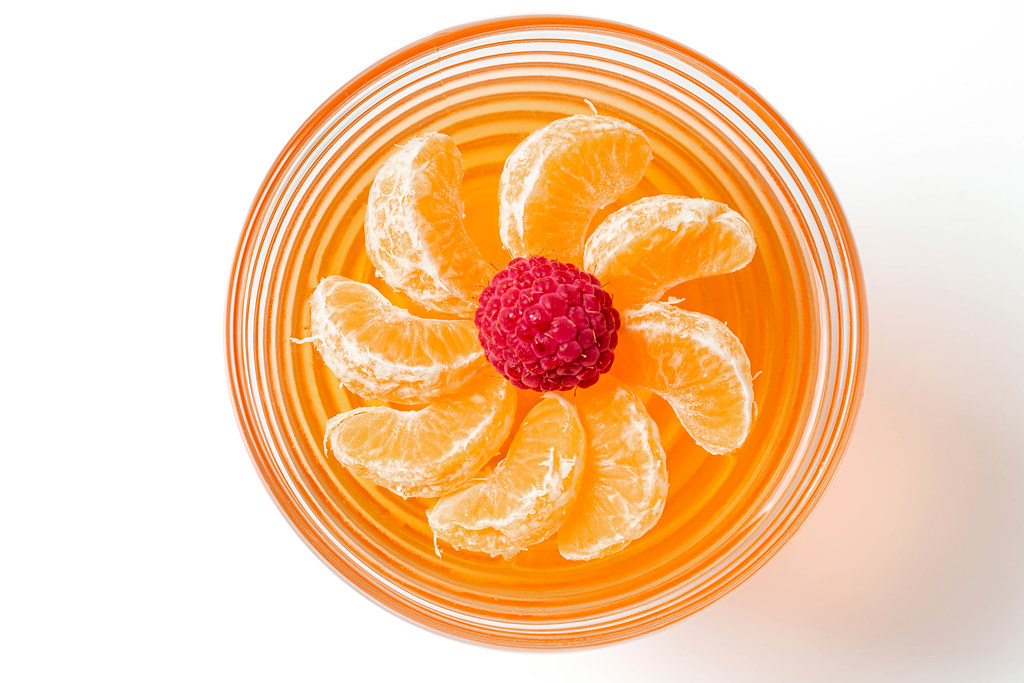 Top view, jelly with fresh tangerine and raspberries