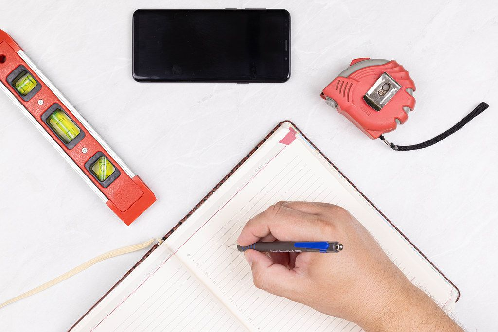Top view Level Measure Tape Mobile phone Hand with Pencil and Paper Notebook