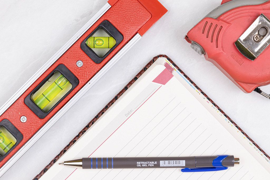 Top view Level Measure Tape Pencil and Paper Notebook