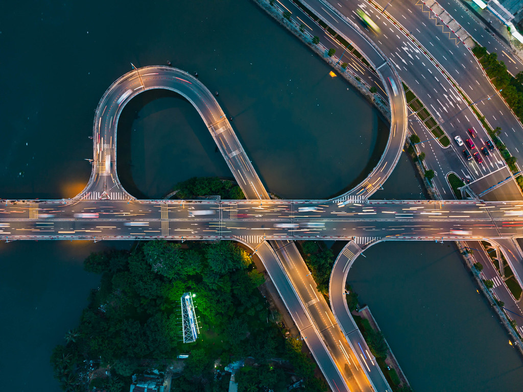 Top View Long Exposure Drone Photo of Traffic on a Bridge over Saigon River with colorful Lights in Ho Chi Minh City, Vietnam