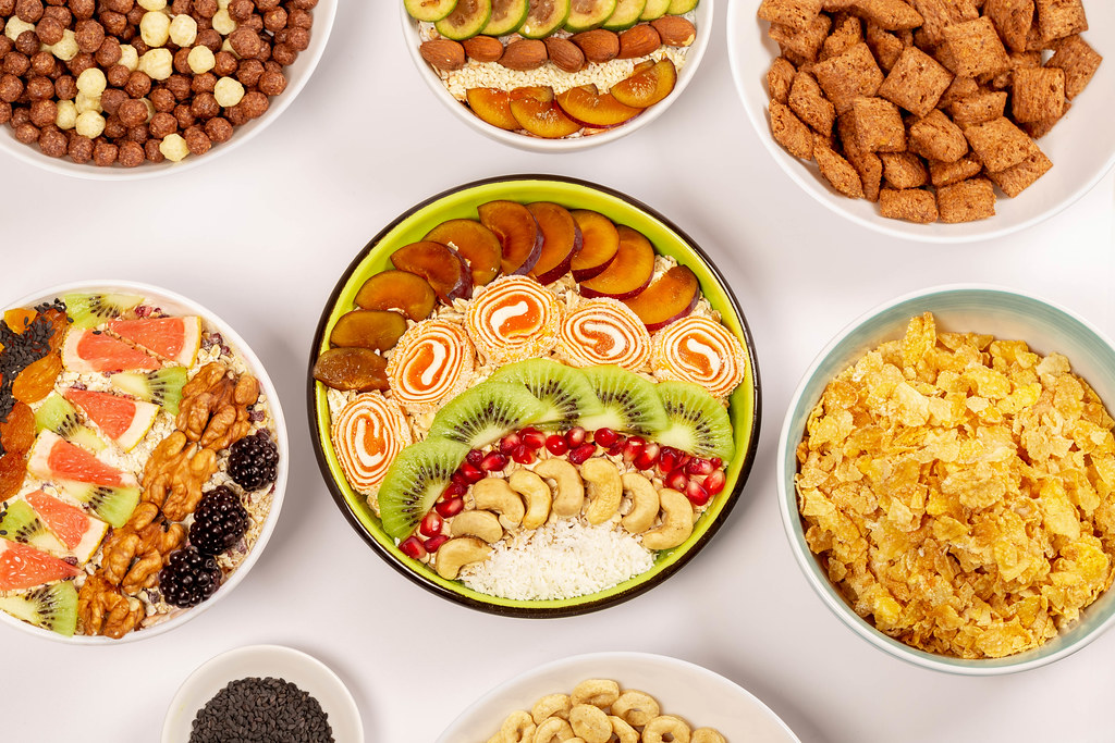 Top view, many bowls of assorted breakfasts, oatmeal, cornflakes and multigrain cereals