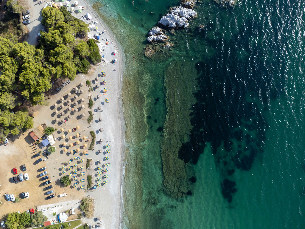 Top view: Milia beach on Skopelos with turquoise water and straw and blue-yellow parasols