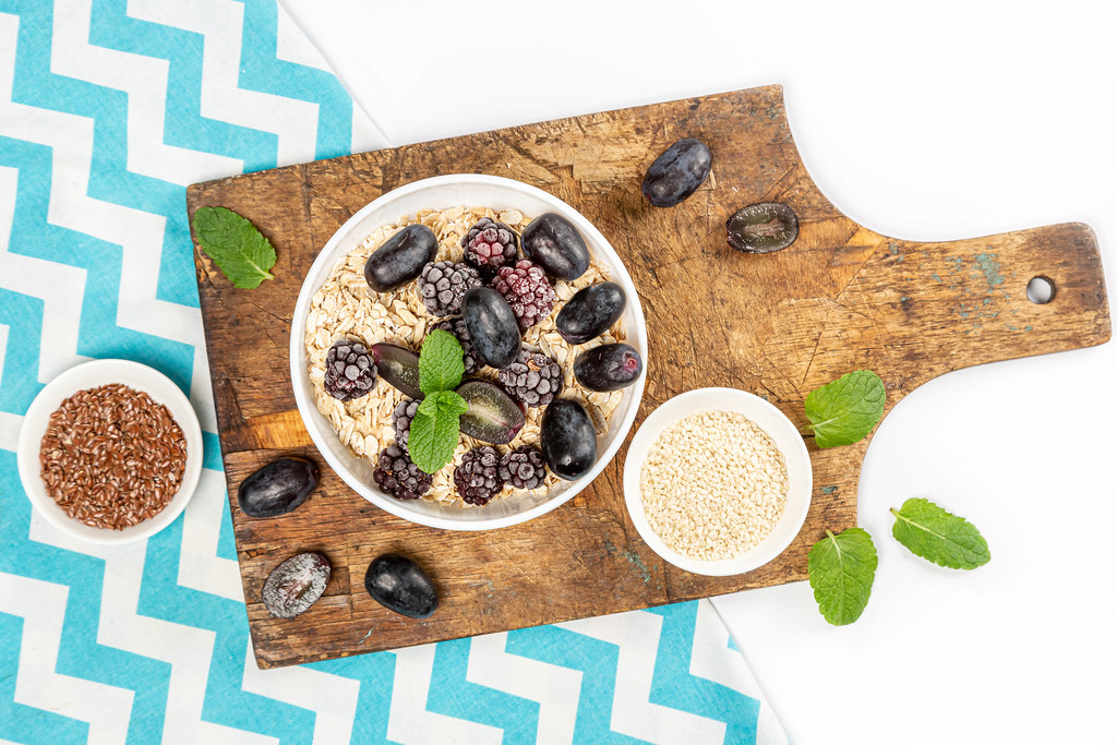 Top view, oatmeal with blueberries and grapes on an old board with fresh mint leaves and seeds