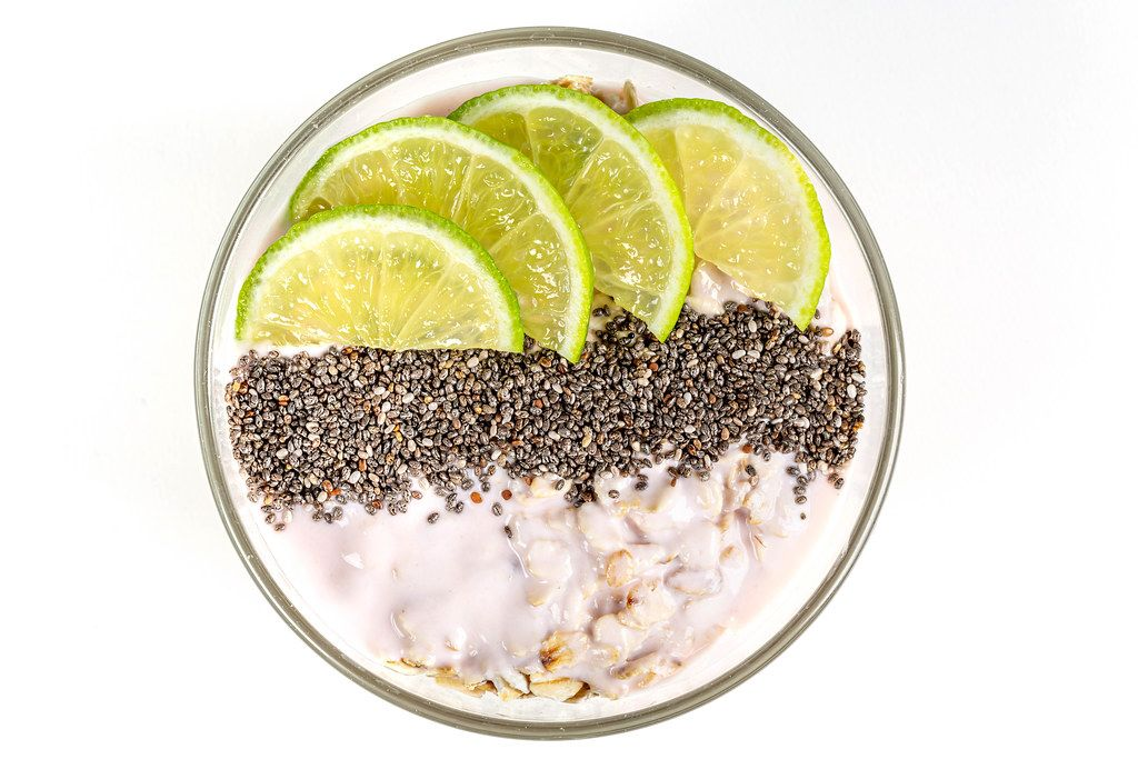 Top view, oatmeal with chia seeds and lime slices on a white background