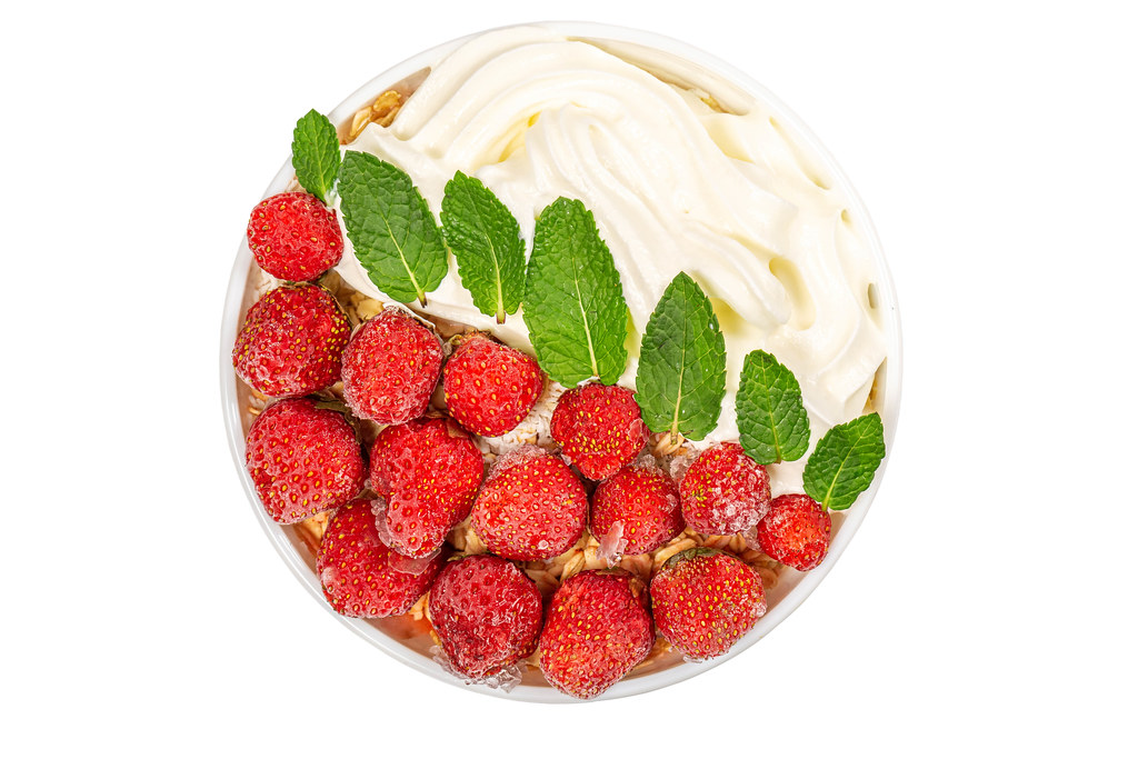 Top view, oatmeal with strawberries, whipped cream and mint on white