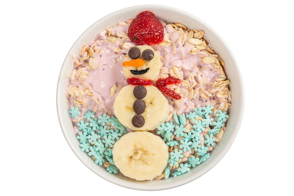 Top view, oatmeal with strawberry yogurt and banana snowman