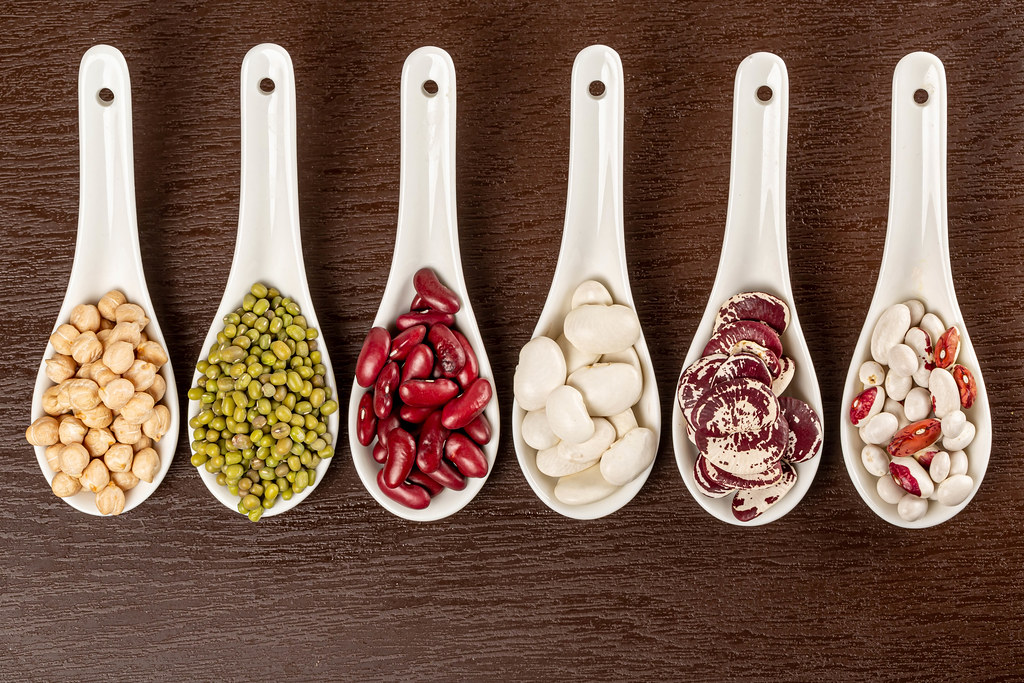 Top view of beans, chickpeas and mung in white spoons on brown background