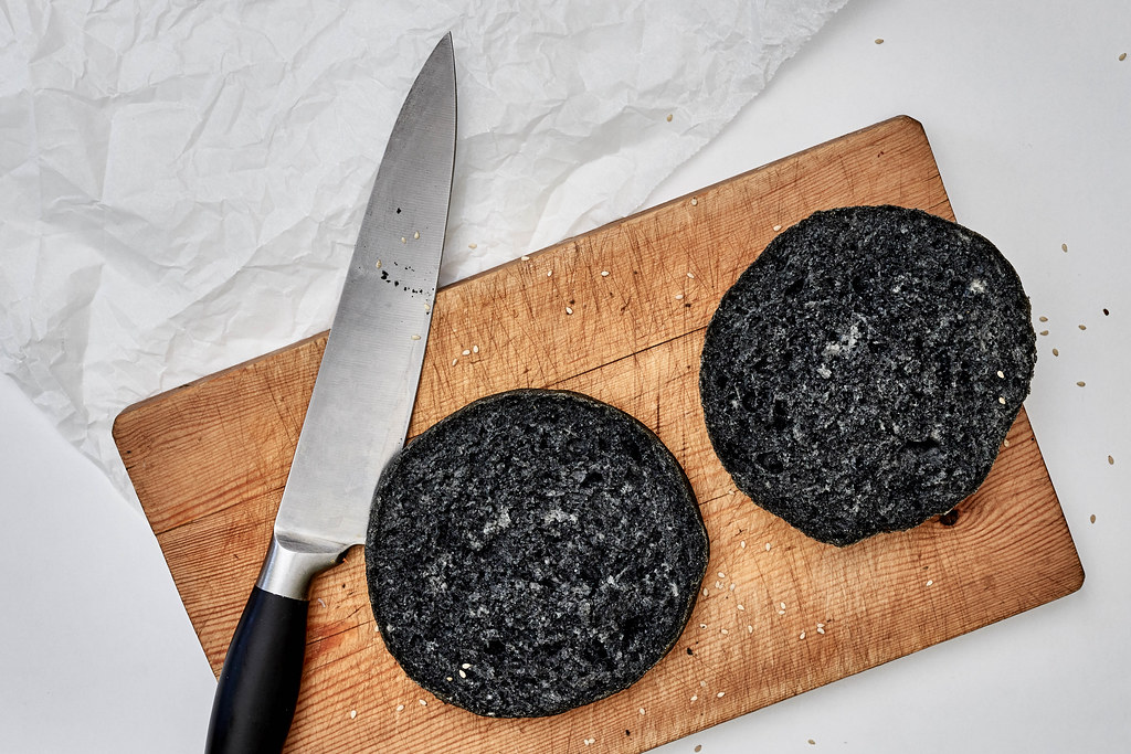 Top view of black hamburger bread sliced on the wooden cutting board