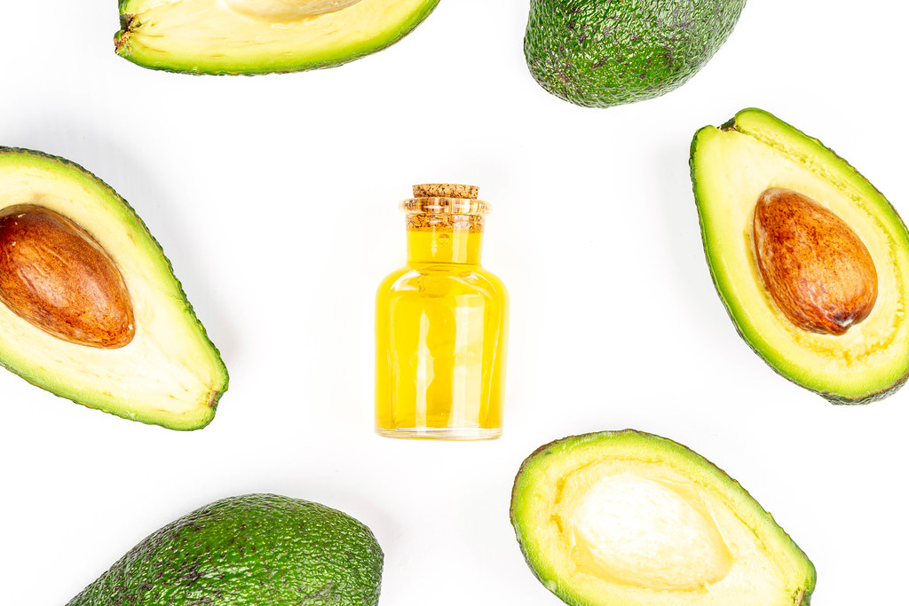 Top view of fresh avocado frame and bottle with oil on white background