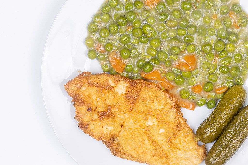 Top view of Fried Chicken breasts with cooked Green Peas