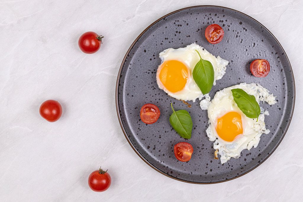 Top view of Fried Eggs served with Cherry tomatoes and Basil