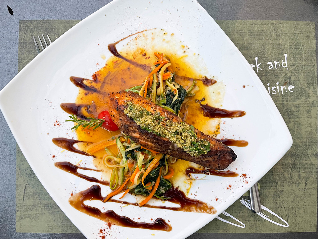 Top view of grilled salmon with veggies, herbs and sauce at Olivo Restaurant on Skopelos