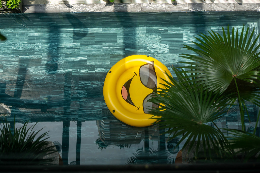 Top View of Large Smiley Pool Ring in a Swimming Pool with Plants and Sunlight at Chi House Hotel in Danang, Vietnam