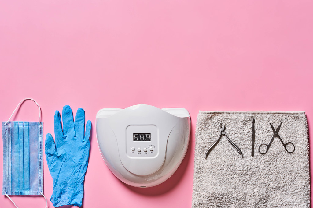 Top view of manicure and pedicure tools on pink background
