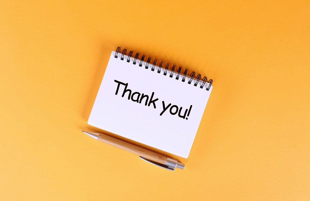 Top view of notebook with Thank you text on orange background