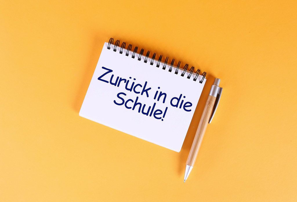 Top view of notebook with Zurück in die Schule text on orange background