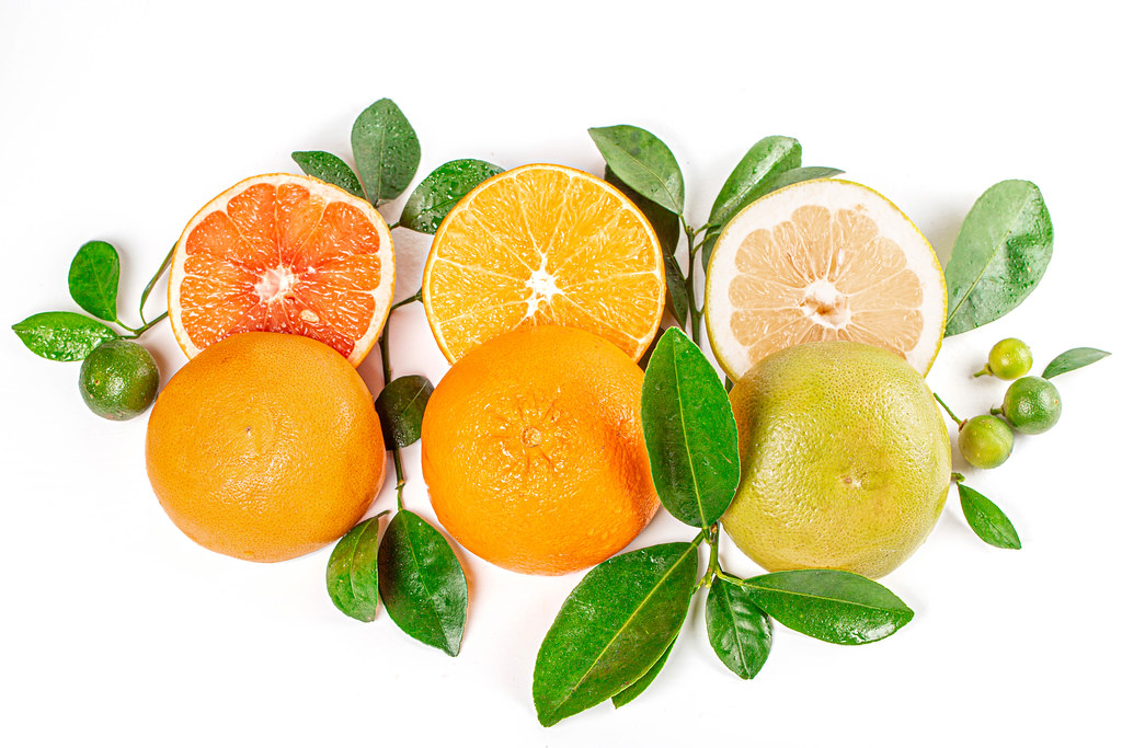 Top view of orange, sweetie, grapefruit and calamondina with branches