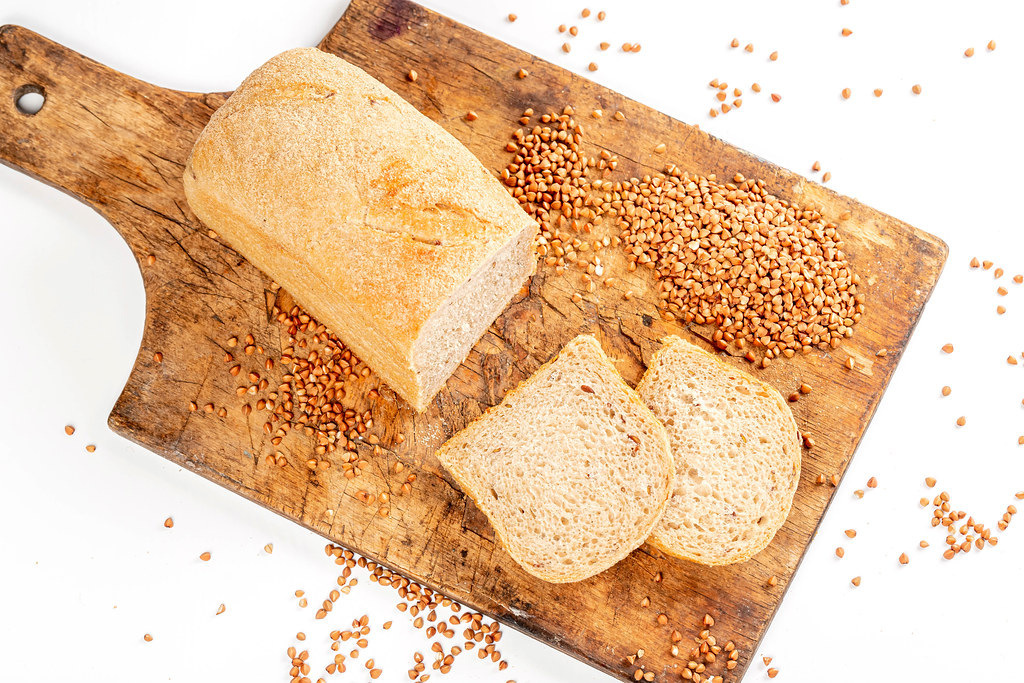 Top view of sliced buckwheat bread on wooden kitchen board with sprinkled buckwheat