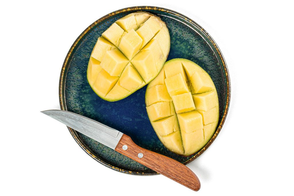 Top view of sliced mango on a plate with a knife