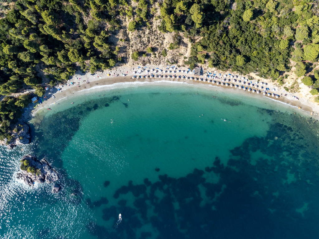 Top view of Stafylos beach with shallow, turquoise waters and wooded hills. Drone photography in Greece