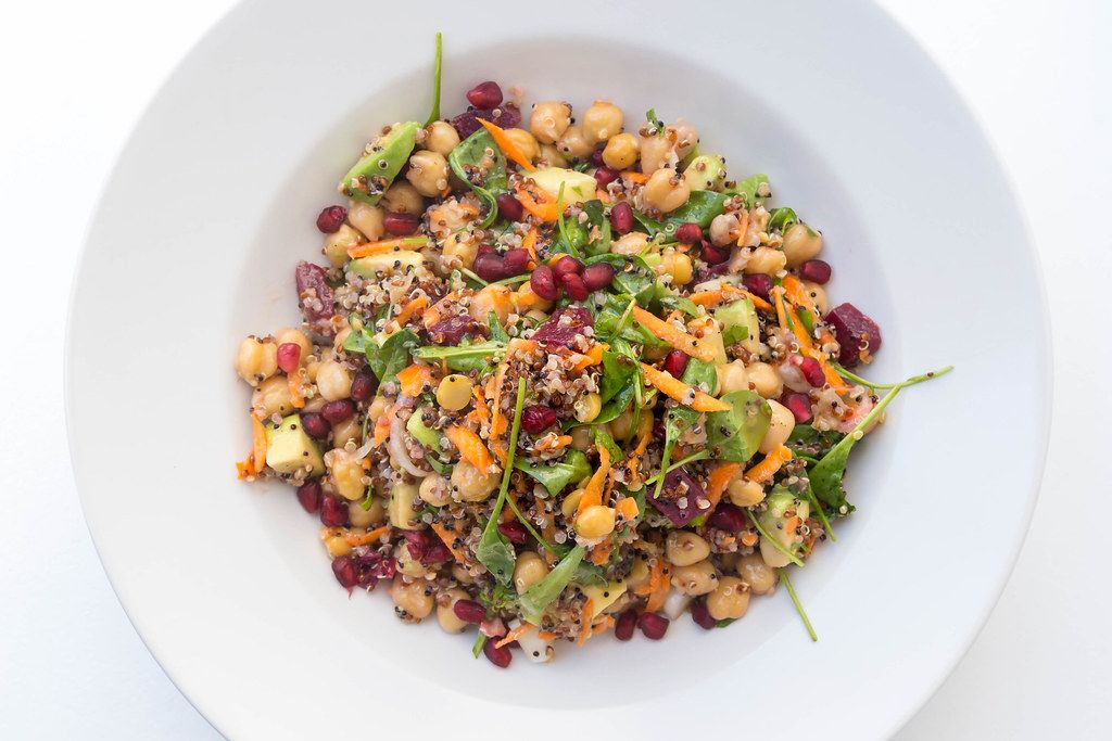 Top view of vegan dish with chickpeas, red beetroot, carrot, avocado, quinoa, spinach and herbs