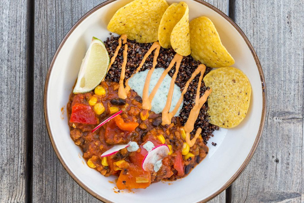 Top view of vegan Mexican food on Mallorca: Tex-Mex stew with black beans, corn, quinoa and nachos