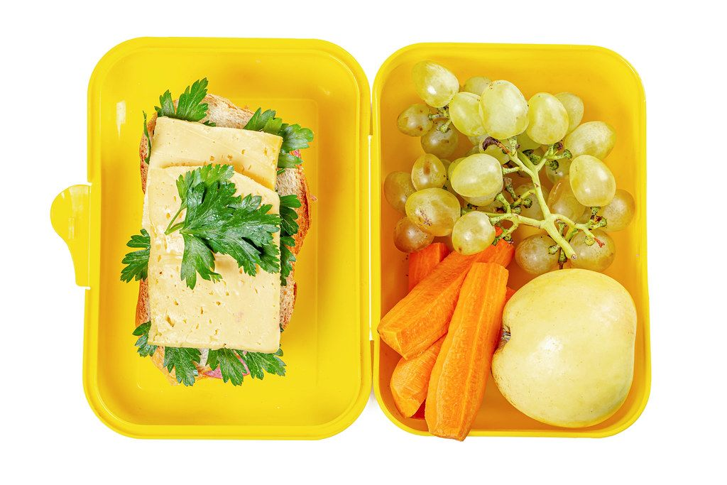 Top view, open lunch box with sandwich, carrots and fruits