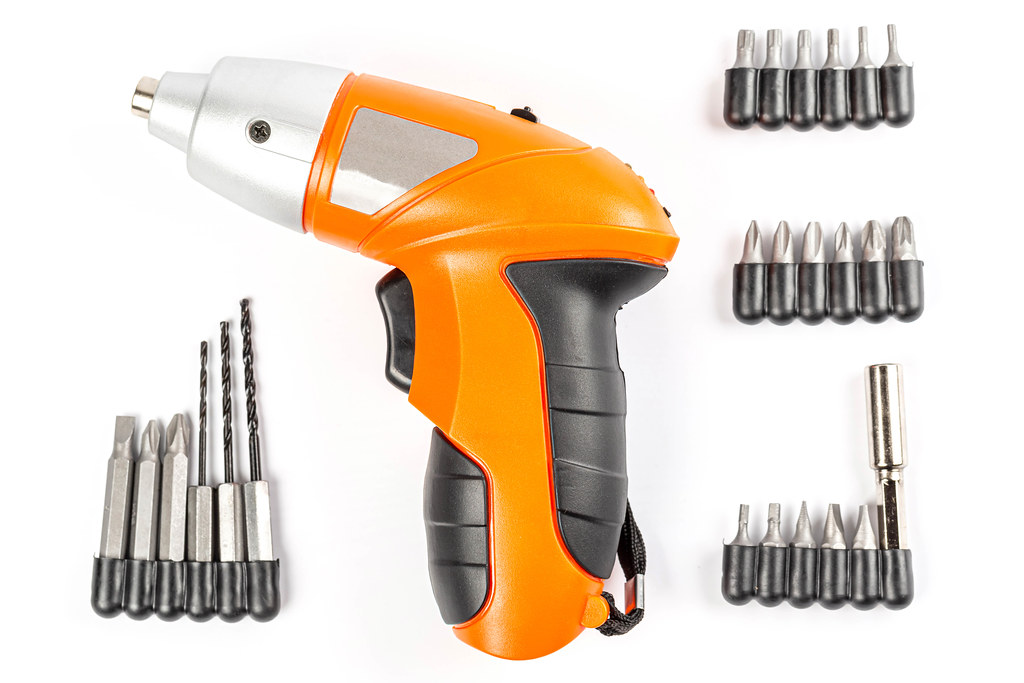 Top view, orange electric screwdriver with bits and drills on white