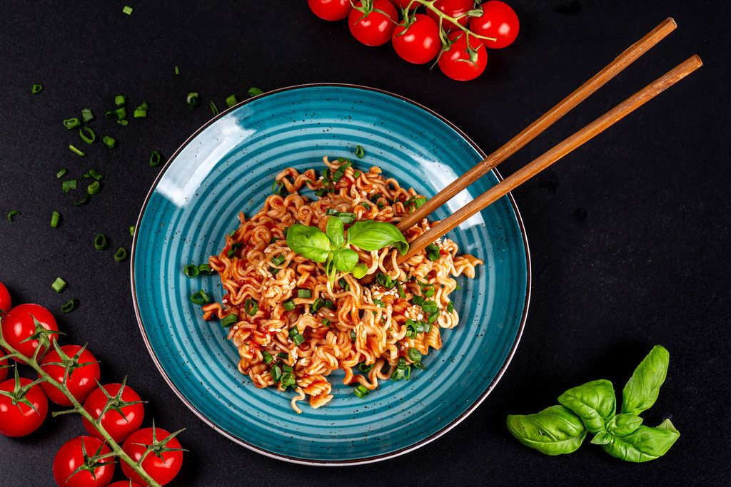 Top view, pasta with sauce, tomatoes and basil on a black background