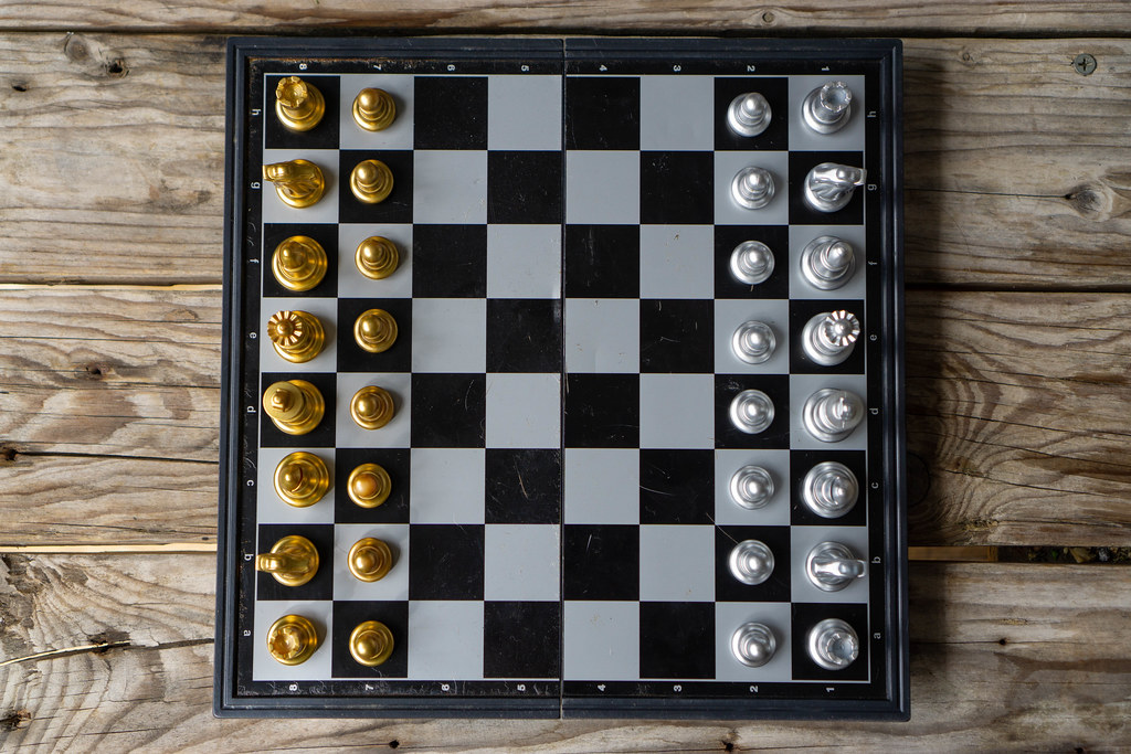 Top View Photo of a Portable Chess Board with Magnetic Chess Pieces in Silver and Gold in Starting Position on a Wooden Table