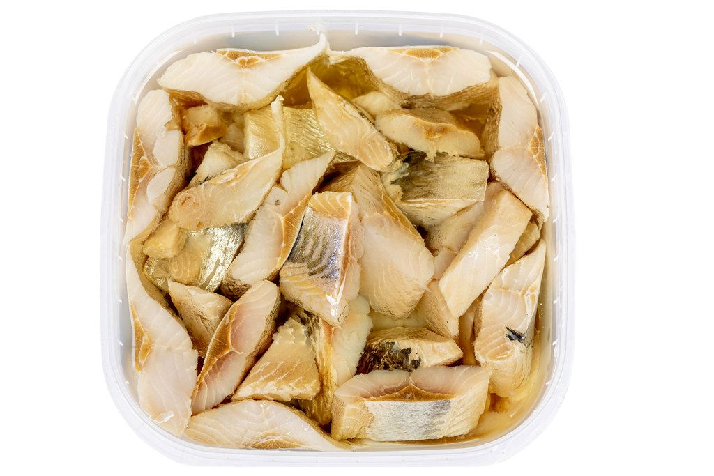 Top view, pieces of pickled herring in oil