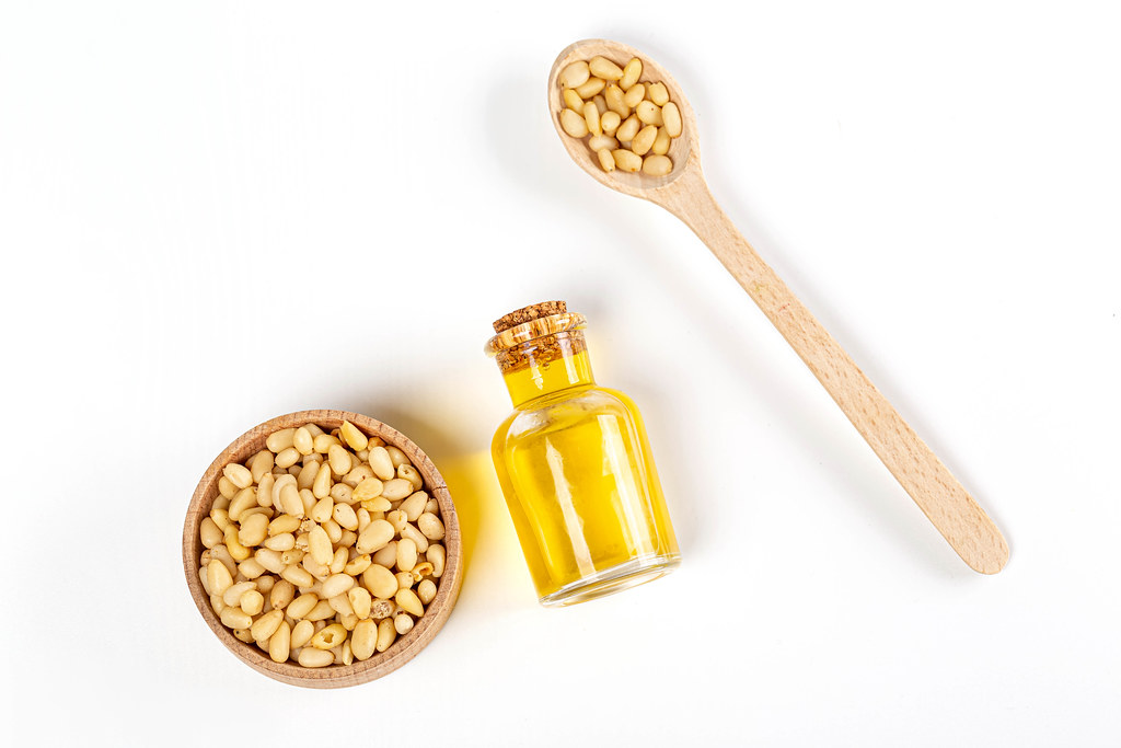 Top view, pine nut oil in bottle with pine nuts in wooden spoon and bowl