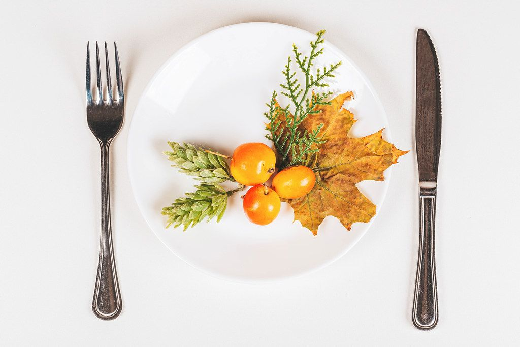 Top view, plate with knife and fork with autumn decor