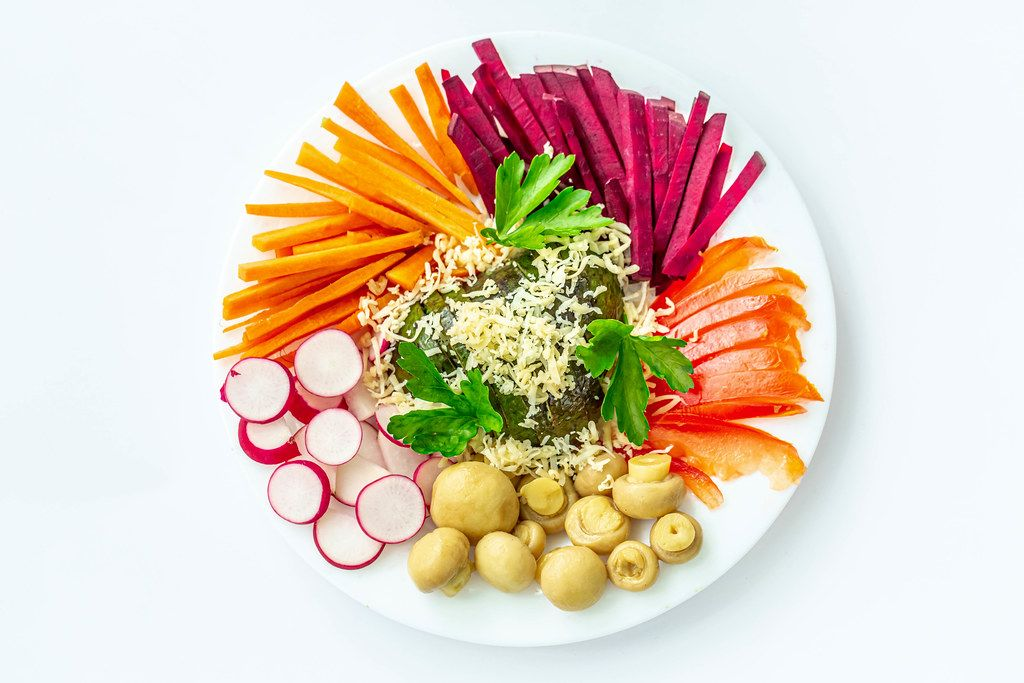 Top view, plate with vegetables and mushrooms on a white background